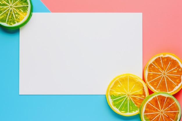Белая рамка бумаги с ломтиком лимона на фоне розового и синего пастельных тонов