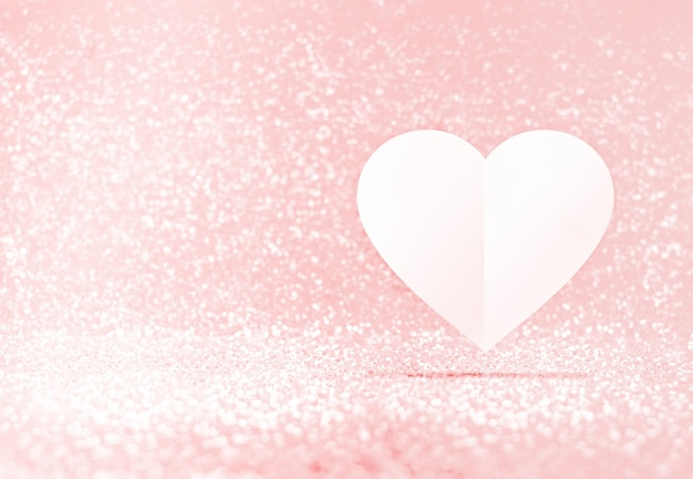 白い紙の心臓の形がパステルピンクのボケの部屋に浮かぶ