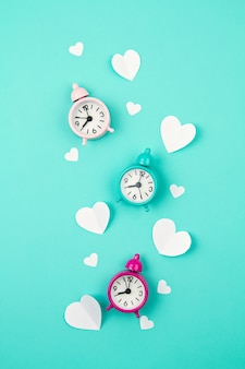 White paper hearts, alarm clocks and clouds. sainte valentine, mother's day, birthday greeting cards, invitation, celebration concept