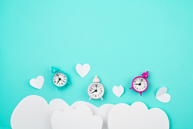 White paper hearts, alarm clocks and clouds over the tuquiose background