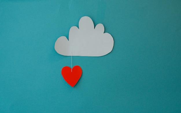흰색 종이 마음과 파란색 배경에 구름. 종이 컷 아웃 수치와 추상적인 배경입니다. 세인트 발렌타인, 어머니의 날, 생일 인사말 카드, 초대장, 축하 개념