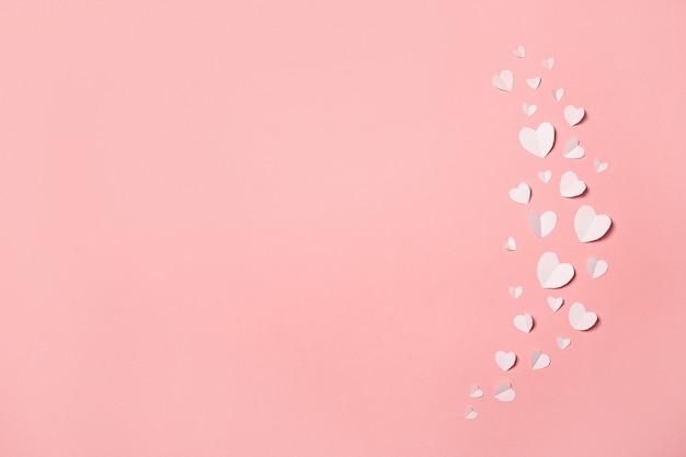 ピンクの背景に白い紙のハート。バレンタインデーの構成。バナー。フラットレイ、上面図。