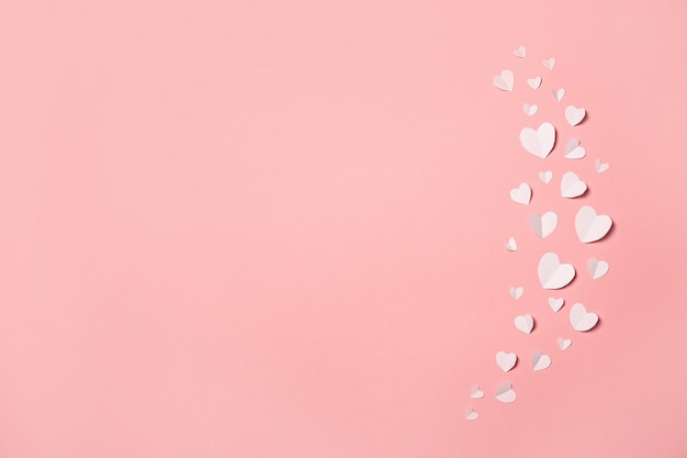 White paper hearts on a pink background. composition of valentine's day. banner. flat lay, top view.