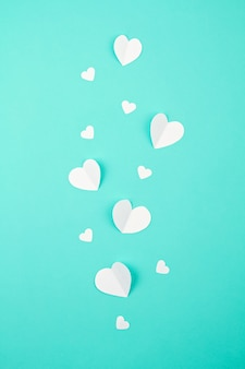 White paper hearts over the turquoise background. sainte valentine, mother's day, birthday greeting cards, invitation, celebration concept