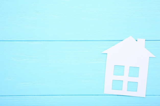 White paper house on a blue background