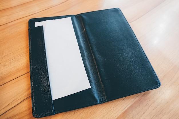 木のテーブルの上の黒い革の支払い請求領収書フォルダの白い紙