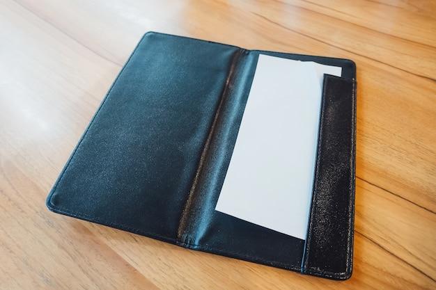 Белая бумага в черной кожаной папке с квитанцией о выставлении счетов