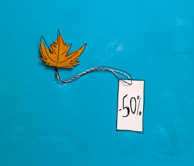 White paper label with inscription 50 percent off sale and maple leaf on turquoise