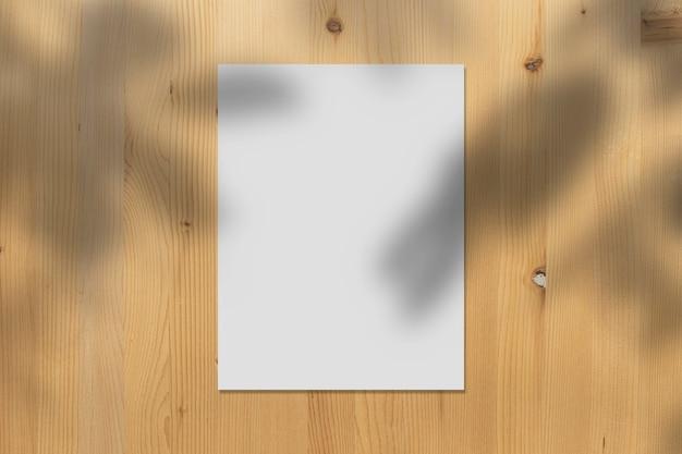 リアルな影で木製の壁に表示される白い紙のモックアップは、ベージュの背景、プロモーションマーケティングのバナー、美的創造的なデザインの背景に葉をオーバーレイします