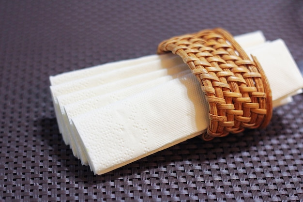 ナプキンリングの白い紙ナプキン。カフェやレストランのテーブル。