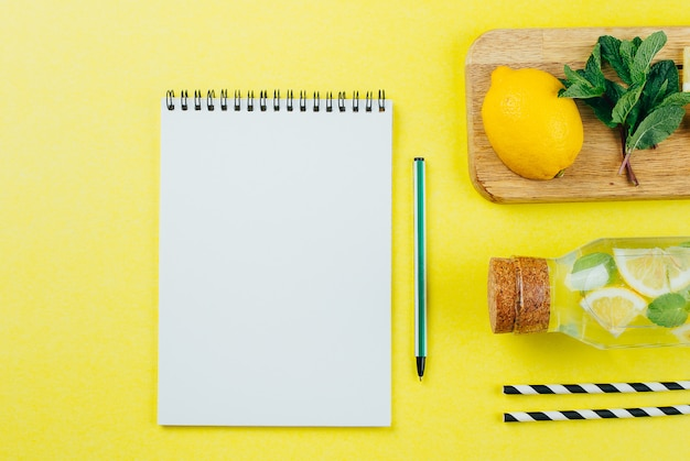 White paper notebook and lemonade with ingredients.
