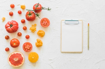 White paper on clipboard with pencil and vegetables on textured backdrop