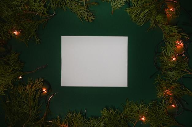 Белая бумага на зеленом в рамке ветвей ели