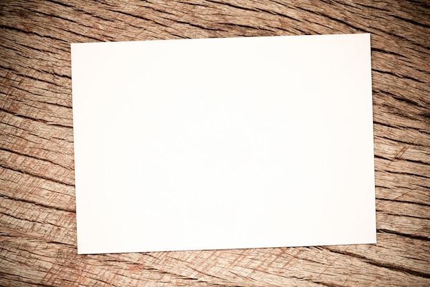素朴な木材に関するホワイトペーパー。テーブルアートツールホワイトシートテキストの木製テーブルの上の紙