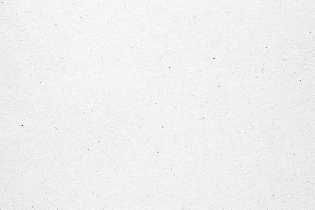 黒い斑点の背景を持つ白い紙または段ボールのテクスチャ。