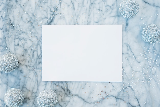 White paper between ornament snowballs and confetti