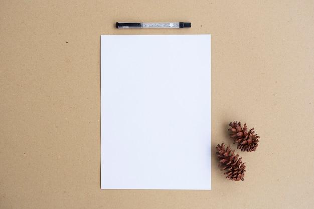 Белая бумага, цветы сосны и ручка на фоне коричневой бумаги. минималистский стиль