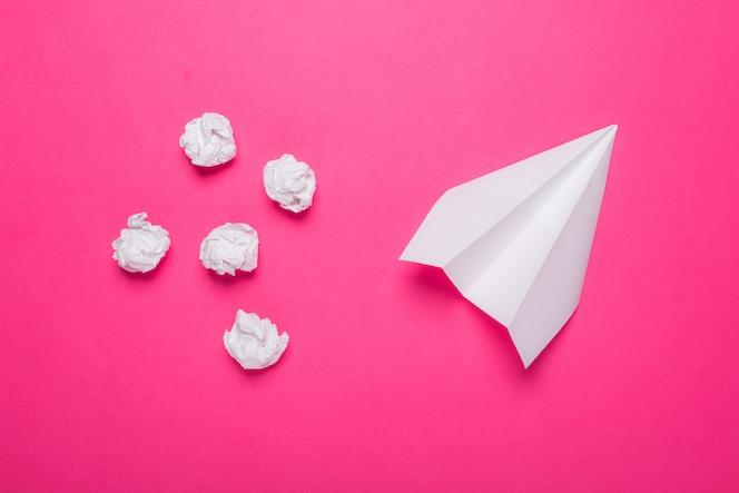 백서 비행기와 분홍색 배경에 구겨진 된 종이 공