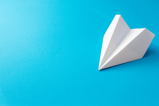 White paper plane on blue background. concept travel illustration