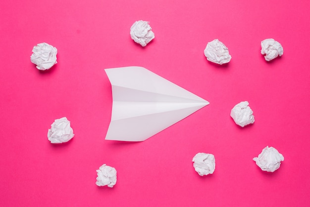 White paper plane and crumpled paper balls on pink