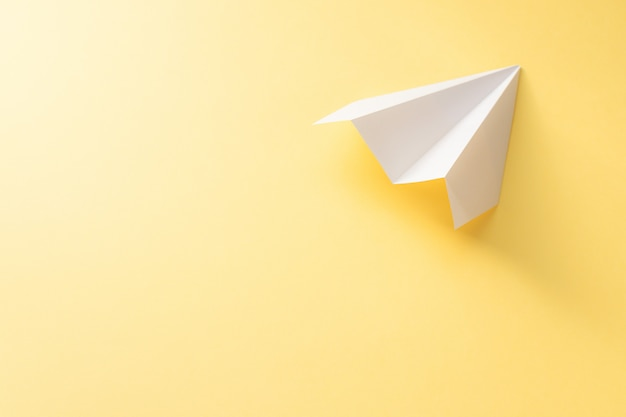 노란색 배경에 백서 비행기입니다. 다채로운 여행 컨셉