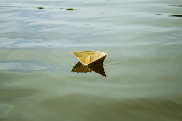 A white paper ship floating on water