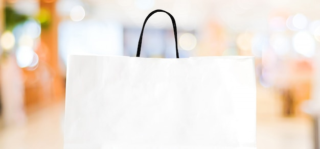 White paper shopping bag over blurred store with copy space