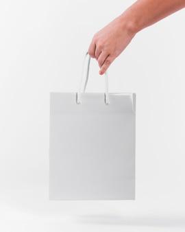 Белая бумажная сумка для покупок, которую держит человек