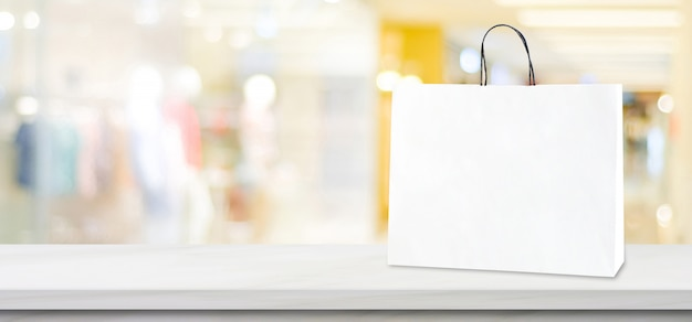 White paper shopping bag standing on white marble table