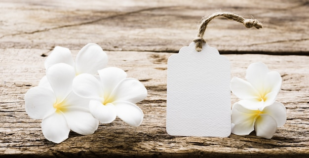 White paper tag label decorate with plumeria flowers on rustic wood table