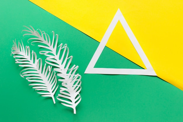 White paper triangle and two paper feathers on green yellow
