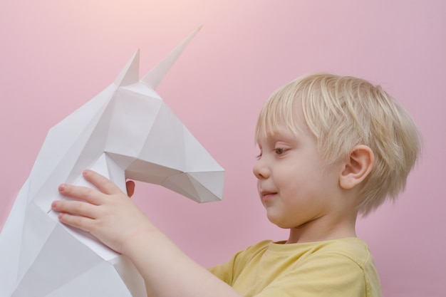 Единорог белой бумаги и маленький белокурый мальчик