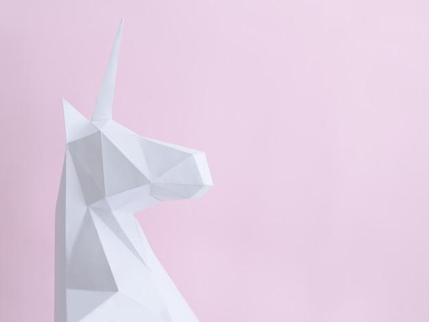Белый бумажный единорог на розовом фоне
