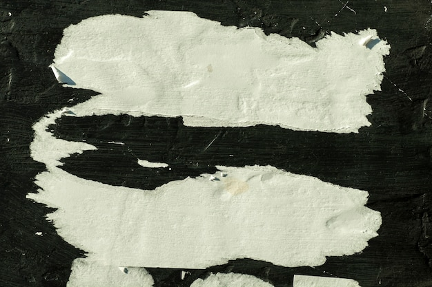 White paper with folds on the black wall.