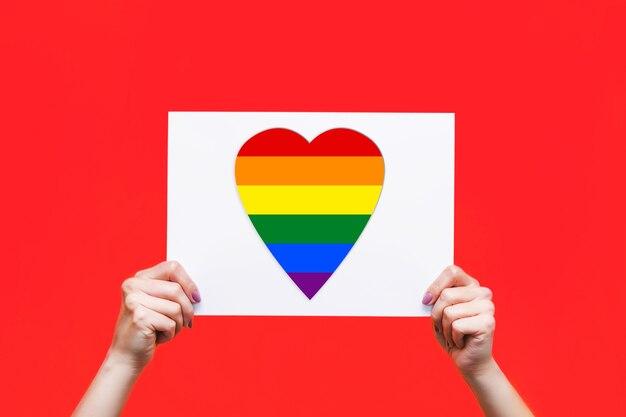 Белая книга с флагом в форме сердца лгбт в женских руках, изолированные на красном фоне