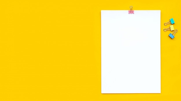 White paper with paperclip on yellow background.