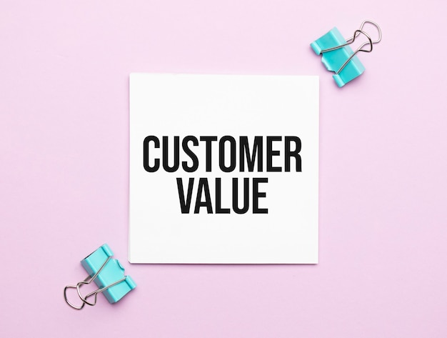 White paper with text customer value on a pink background with stationery