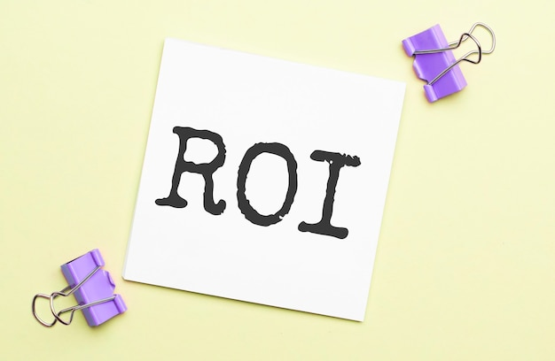 White paper with text roi on a yellow background with stationery