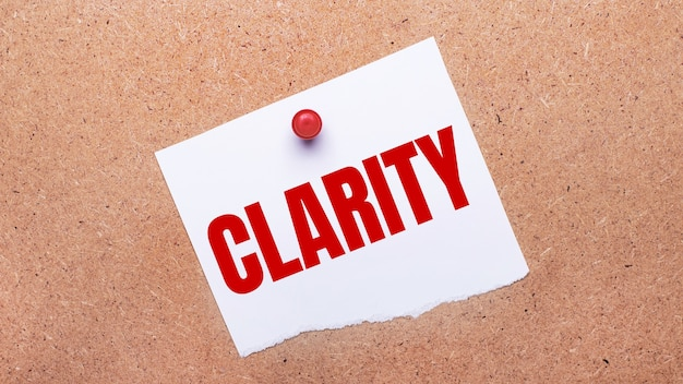 Белая бумага с текстом ясность прикреплена к деревянному фону с помощью красной кнопки.