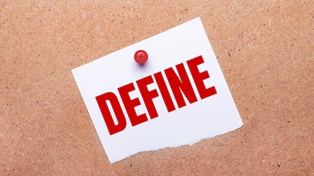 Белая бумага с текстом define прикреплена к деревянному фону красной кнопкой.