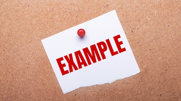 例のテキストが付いた白い紙は、赤いボタンで木製の背景に添付されています。