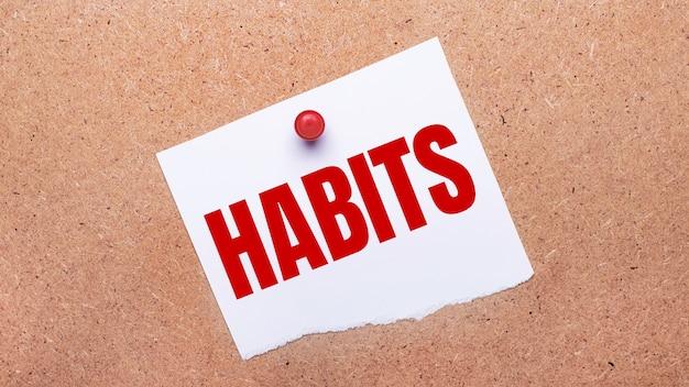 Habitsというテキストの白い紙が赤いボタンで木製の背景に添付されています。