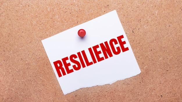 Белая бумага с надписью resilience прикреплена к деревянному фону с помощью красной кнопки.