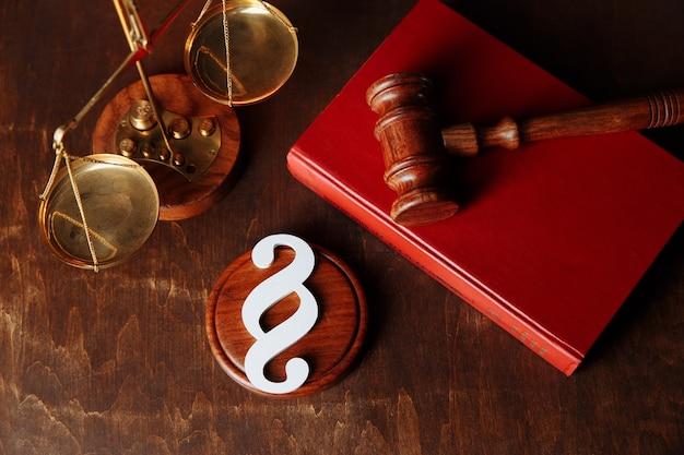 Белый символ абзаца и молоток судьи в книге закона