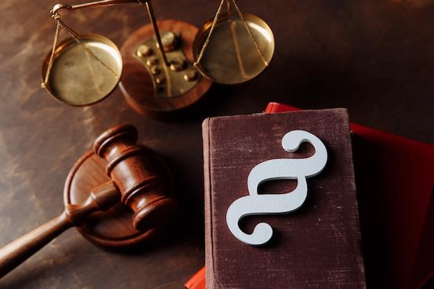 Белый символ абзаца находится на книге законов и молотке в зале суда.