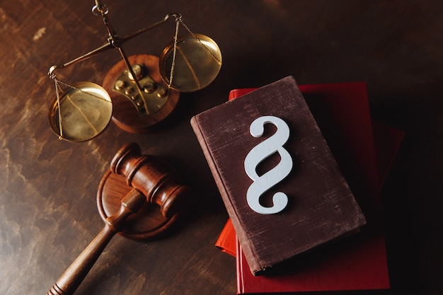 White paragraph symbol is on red law book and gavel in courtroom.