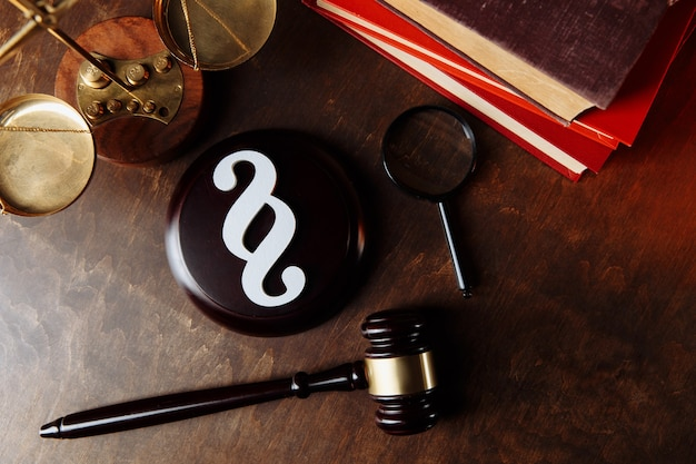 White paragraph symbol and judge gavel with scales and books at lawyer office.