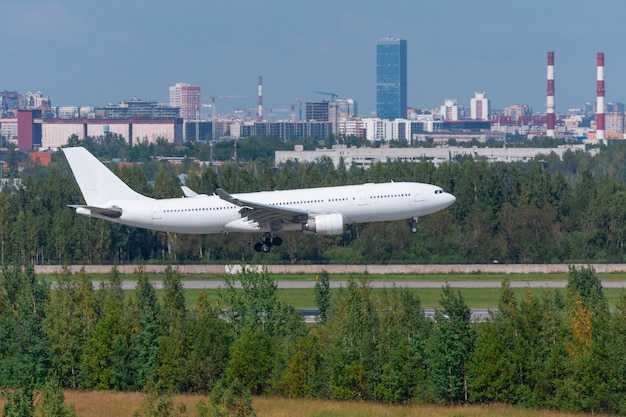 White passenger airliner landed on runway at the airport against the background of the city.