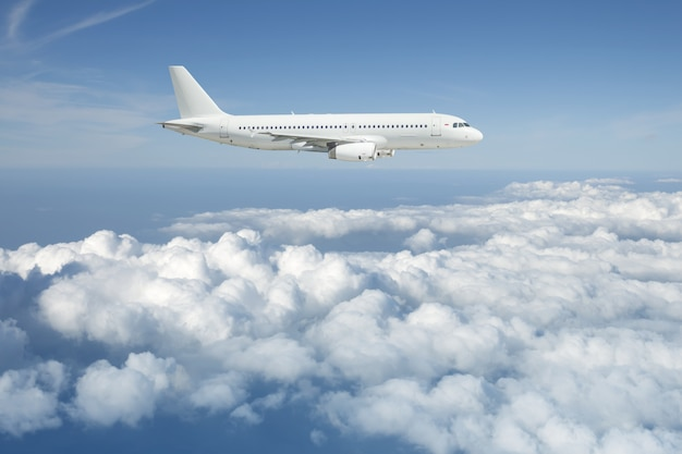 White passenger airplane is flying over the cloudy sky.