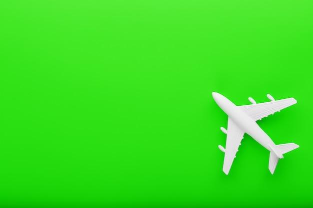 明るい緑の背景に白い乗客模型飛行機